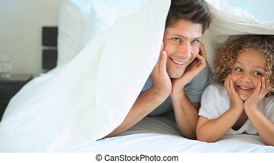 A family under the bed sheets smiling