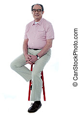 Confident senior man resting on stool - Confident senior man...