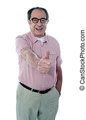 Smiling aged male gesturing thumbs-up, portrait