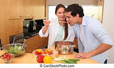 Talking couple in the kitchen tasting the food