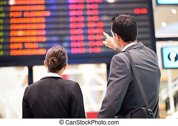businessman and businesswoman checking flight information at airport