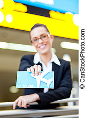 young businesswoman presenting air ticket at airport, focus on foreground