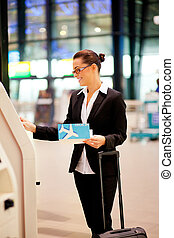 self help check in at airport - businesswoman using self...