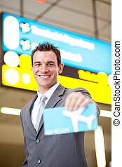 happy young businessman presenting air ticket