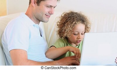 Father and son watching video on a laptop in the living room