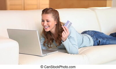 Young woman holding a credit card while shopping online