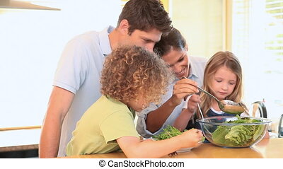 Family mixing lettuce in the kitchen