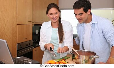 Couple cooking while reading the recipe on a laptop in a...