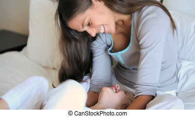 Mother tickling her daughter