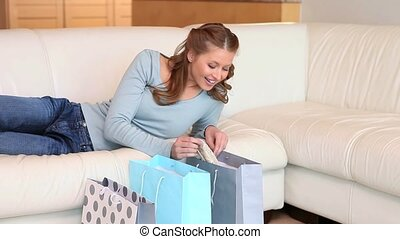 Young woman looking into her shopping bag while lying on a...