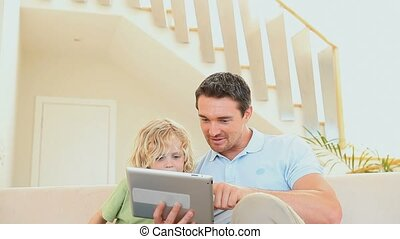 Son and father using a tablet computer