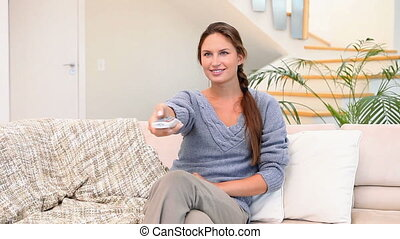 Woman using a remote control to turn on the television