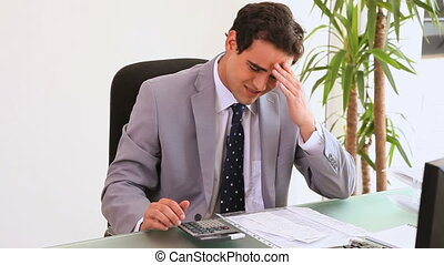 Worried businessman using a calculator