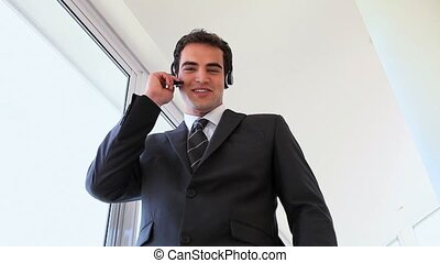 Businessman using headset while standing