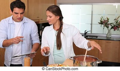 Couple looking a recipe on a tablet computer while cooking