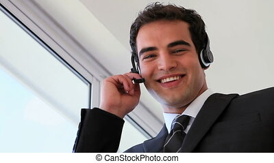 Businessman wearing headset while laughing in a building
