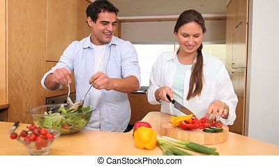 Couple cooking lettuce in the kitchen