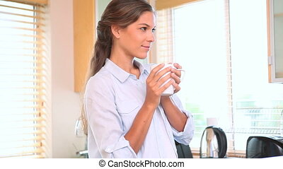Woman drinking a coffee in her kitchen