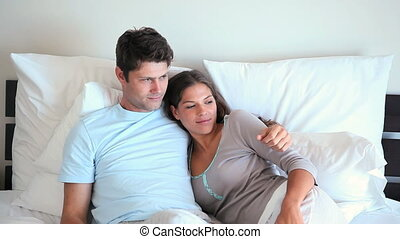 Smiling couple in their bed while their son is doing a...