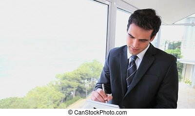 Businessman writing on a notepad - Frustrated businessman...