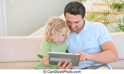 Father and son using a tablet computer in the living room