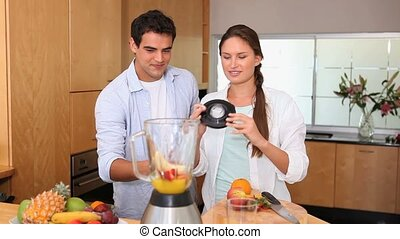 Couple putting fruits in a blender in the kitchen