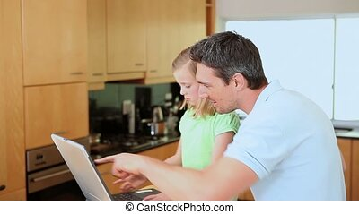 Father and daughter using a laptop
