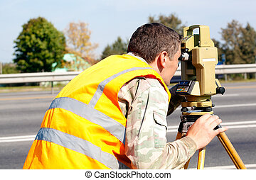 Surveyor looking into theodolite - Surveyor engineer making...