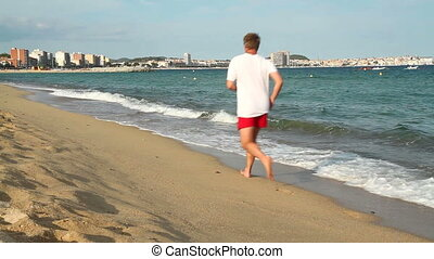 Runner - Young man running on the beach