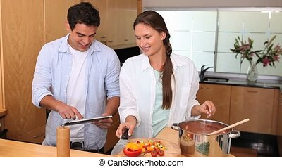 Couple cooking with a tablet computer