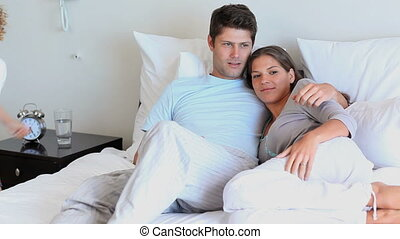Couple lying on their bed while their son comes and jump on...