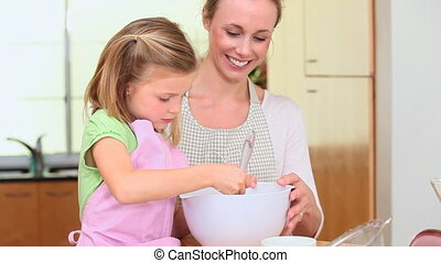 Girl cooking with her mother