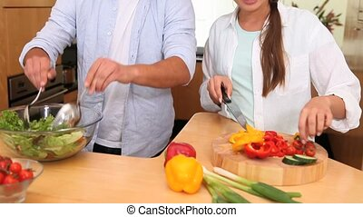 Couple preparing a salad in the kitchen