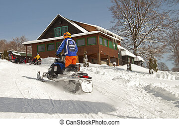Going up on a snowmobile - A man is going up a hill on a...