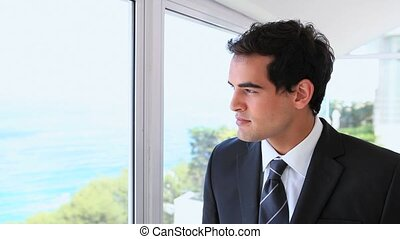 Businessman drinking from a mug while looking out a window