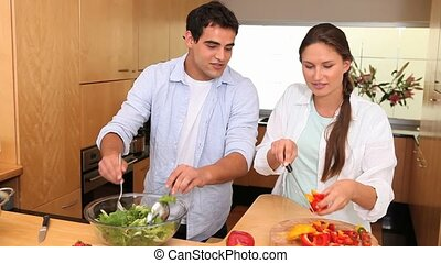 Couple preparing a salad with peppers in a kitchen