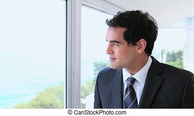 Businessman drinking coffee while looking outside