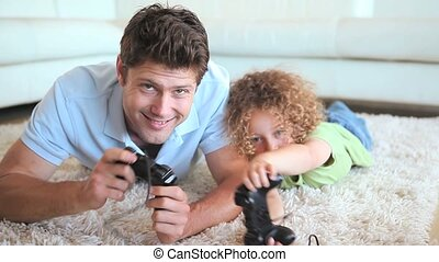 Father and son playing video game lying on a carpet