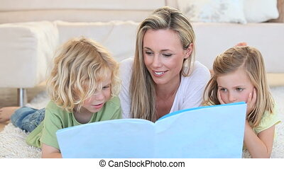 Mother showing an image in a book to her children while...