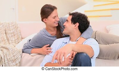 Cute couple smiling at each other in the living room