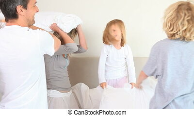 Family having a pillow fight in the parents bedroom