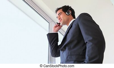 Standing man speaking in headset near a window