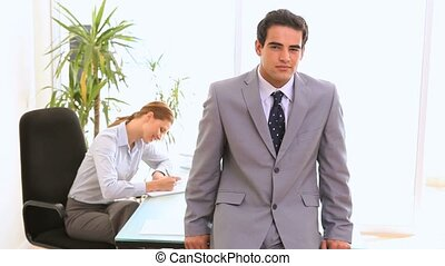Businessman posing while his colleague is working in...