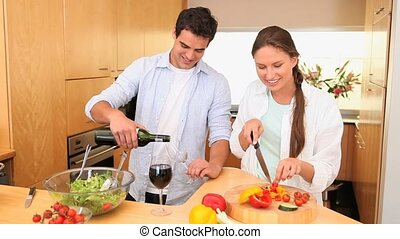 Man serving wine to his wife in the kitchen