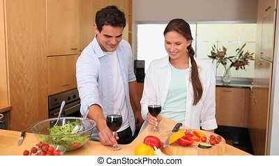 Couple toasting with glasses of wine in the kitchen
