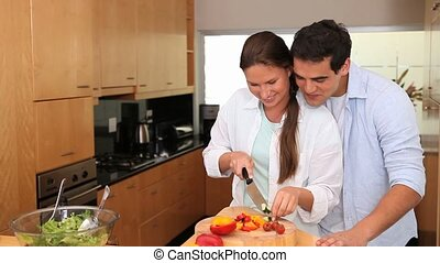 Man embracing his wife who's cooking