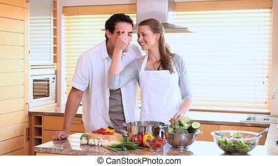 Husband tasting his wifes cooking with a spoon in a kitchen