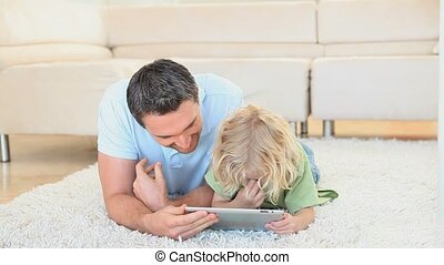 Father with his son using a tablet computer while lying on a...
