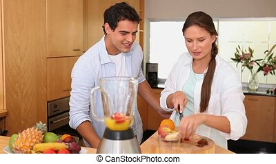 Couple putting fruits into a blender in the kitchen