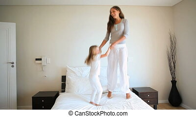 Mother and daughter jumping on a bed in a white hotel room
